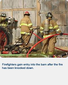 Firefighters gain entry into the barn after the fire has been knocked down.