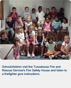Schoolchildren visit Tuscaloosa Fire and Rescue Service's Fire Safety Service House and listen to a firefighter give instructions
