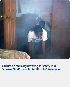 "Children practicing crawling to safety in a ""smoke-filled"" room in the Fire Safety House"