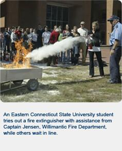 As Eastern Connecticut State University student tries out a fire extinguisher with assistance from Captain Jensen, Willmantic Fire Department, while others wait in line.