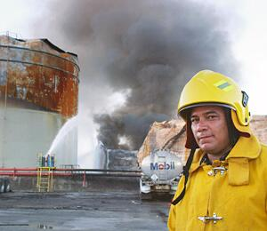 Firefighter standing in front of a gas tank with smoke in the background