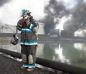 Firefighter standing in front of a water source and burning commercial building in the background with smoke in the air