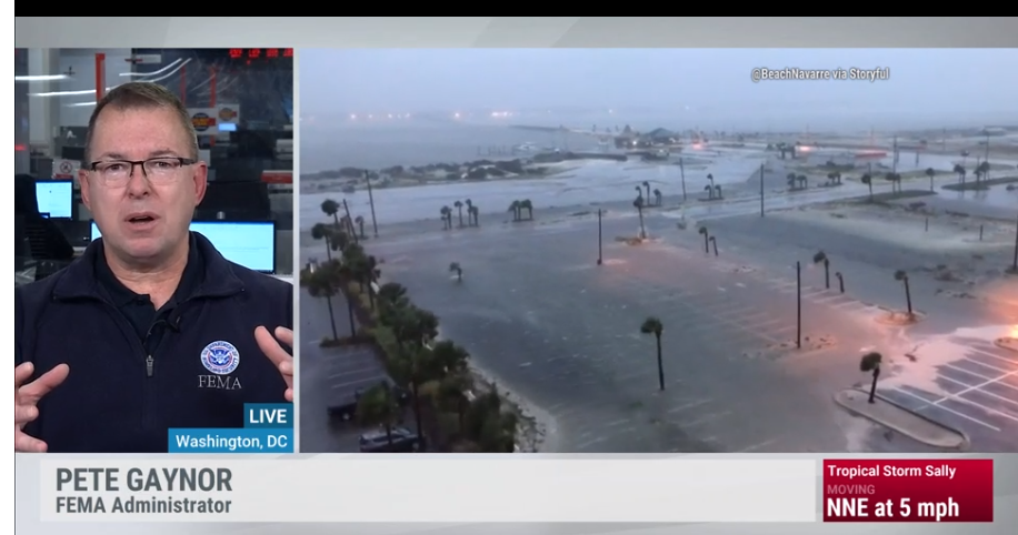 Peter Gaynor on the left talking and flooded streets on the left