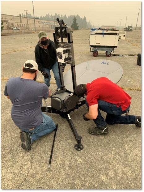 3 people setting up a communications tower