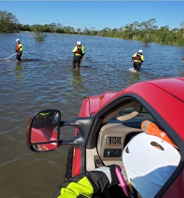 Search and rescue task force members stand in deep water while one members sits in a car