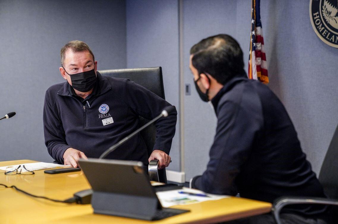 Two men sitting at a conference table are speaking with each other while wearing masks.