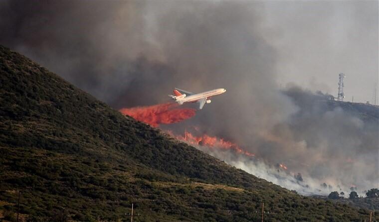 a plane drops water over a fire