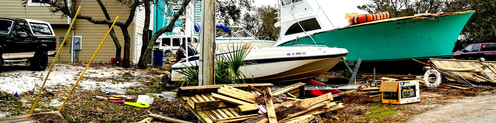 Two big boats beside a house with wood debris everywhere around it