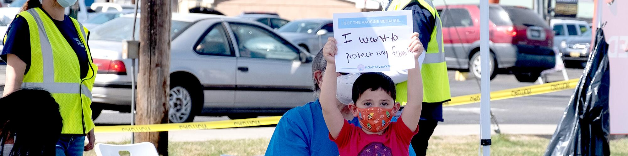 "A little boy holding a signing saying ""I want to protect my family"""