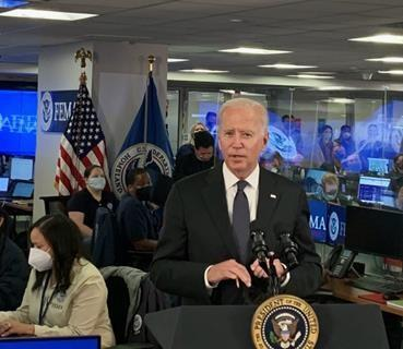President Joseph R. Biden, Jr. talking in front of a podium with multiple fema staff standing beside and behind him in the nrcc