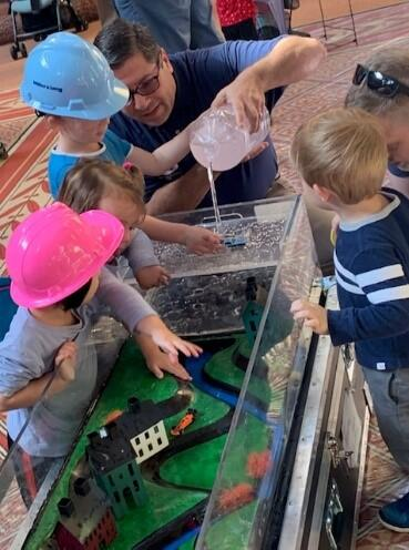 A member of the FEMA Building Science team uses a flood table to demonstrate the effects of flooding to young attendees at the National Building Museum's Big Build Community Day.