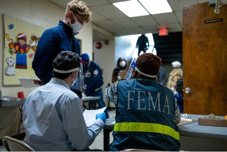 FEMA workers assisting a survivor register for a vaccine.
