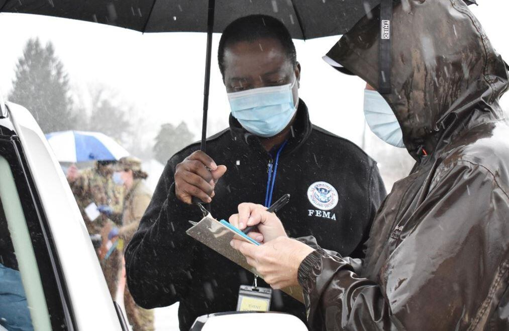 FEMA Worker holding a umbrella and another working signing a survivor up for vaccinations.