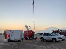 Mobile cellular tower set up on a parking lot with other vehicles parked